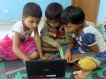 Three children using a computer